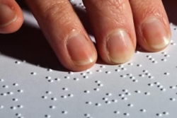 Hand on a page of Braille text