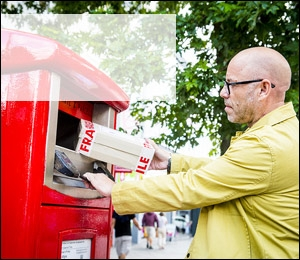 A man posting a parcel in one of Royal Mail's parcel postboxes